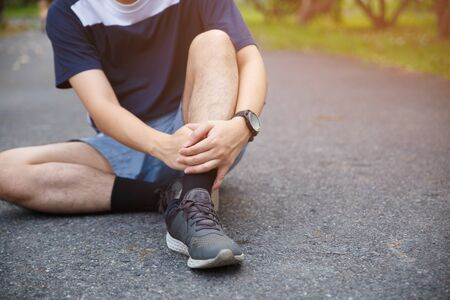 Male runner athlete ankle injury and pain. Man suffering from painful ankle while running in the public park. Reklamní fotografie