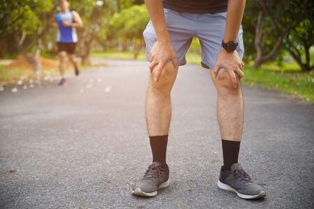 Male runner athlete knee injury and pain. Man suffering from painful knee while running in the public park. Reklamní fotografie