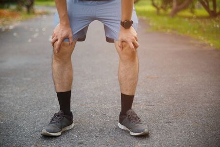 Male runner athlete knee injury and pain. Man suffering from painful knee while running in the public park. 版權商用圖片
