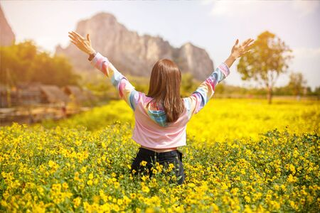 Beautiful girl hands up and looking far away in the yellow flower garden to relax and happy.