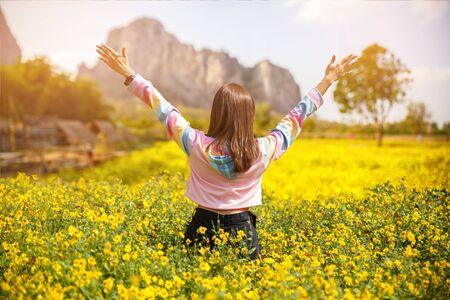 Hermosa chica manos arriba y mirando lejos en el jardín de flores amarillas para relajarse y feliz.