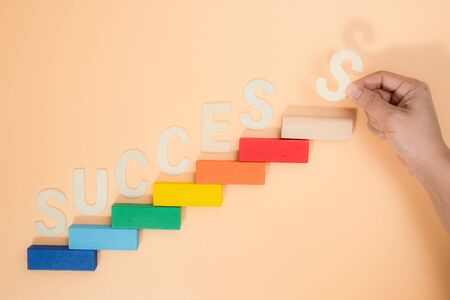 Hand arranging S wood block stacking as step stair. Business concept for growth success process. Stairs up as a symbol of career growth up or business success.