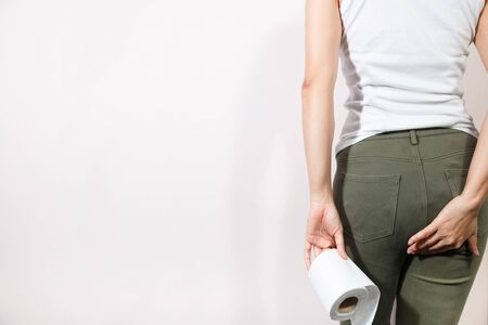 Woman hand holding her bottom and tissue or toilet paper roll. Disorder, Diarrhea, Constipation. Healthcare concept.
