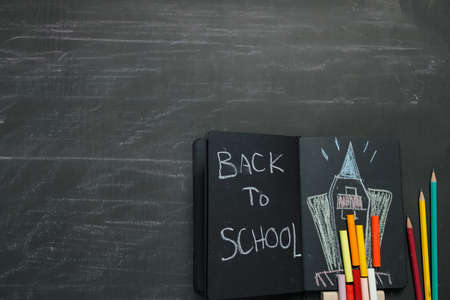 School supplies on black board background. Back to school concept.
