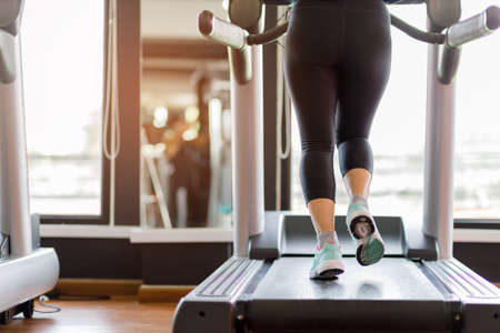 Close up foot sneakers Fitness girl running on track treadmill, Fat woman with muscular legs in exercise gym. Concept of healthy life. 스톡 콘텐츠