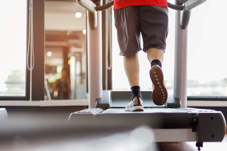 Close up foot sneakers Fitness man running on track treadmill, Man with muscular legs in exercise gym. Concept of healthy life.