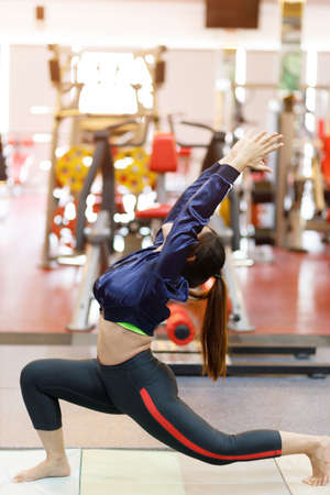 Sporty young woman doing yoga practice in the gym - concept of healthy life and natural balance between body and mental development.
