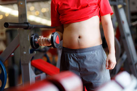 Fit young woman lifting barbells looking focused, working out in a gym.