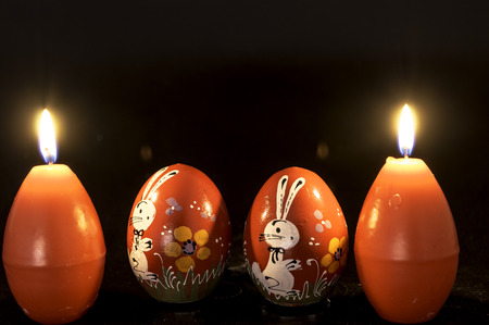 egg shape: red easter egg shape candle burning between two wooden eggs