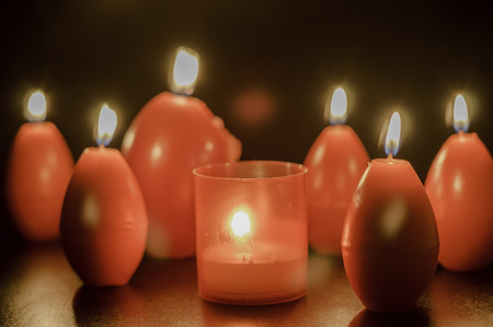 easter candle is burning: red easter egg shape candles burning Stock Photo