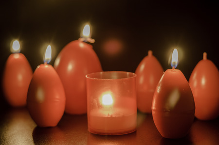 egg shape: red easter egg shape candles burning Stock Photo