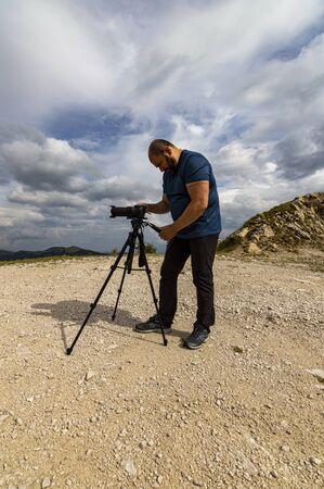 Photographer traveler taking pictures of landscape in the mountains. Tourist on summer holiday vacation