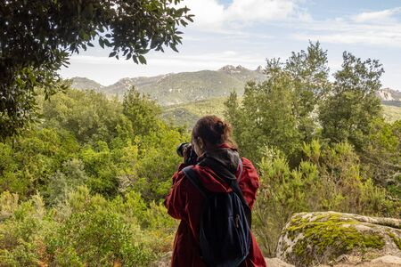 Woman tourist photographer with camera on a mountain outdoors during a hike in autumn