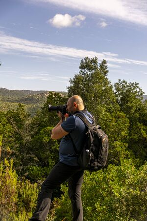 man tourist photographer with camera on a mountain outdoors during a hike in autumn Stok Fotoğraf