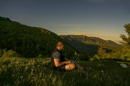 man working outdoors with laptop. Green spring mountain landscape