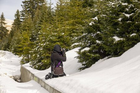 Woman Photographer Hiker In Snowy Mountain, In Search Of Best Picture to Take 写真素材