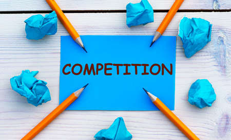 COMPETITION - word on blue paper on a light background with crumpled pieces of paper and pencils. Business concept Stok Fotoğraf