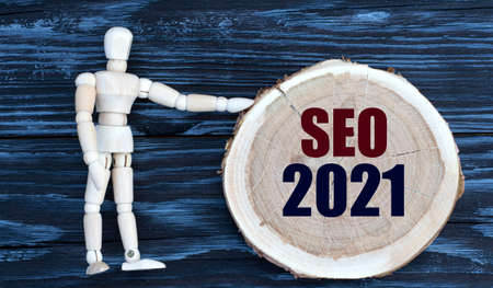 SEO 2021 word on a wooden circle on a dark background with a male figurine. Business concept Banque d'images
