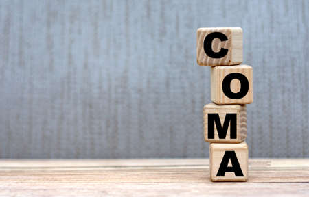 COMA word on cubes on a beautiful gray background. Medicine concept.