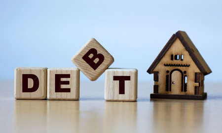 DEBT word on cubes on a light background with a wooden house. Business and finance concept.