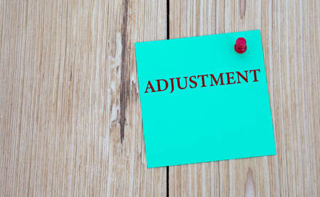 ADJUSTMENT - word written on a green sheet for notes, which is pinned to a light wooden board. Business concept