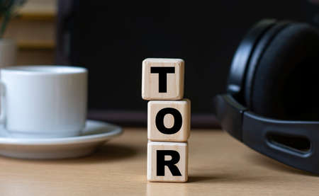 TOR (The Onion Router) -word on cubes on the background of the tablet, headphones and a white cup. Technology and computers concept.