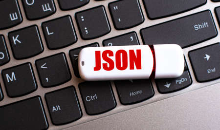 JSON is a word on a white flash drive lying on a black laptop keyboard. Textual data exchange format concept