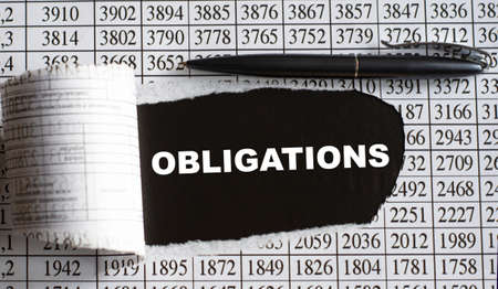 OBLIGATIONS is the word behind torn office paper with numbers and a black pen. Business and finance concept