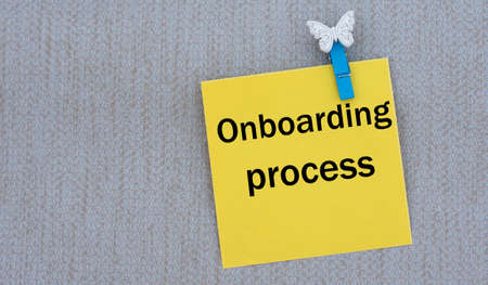 ONBOARDING PROCESS - words on yellow paper with clothespin on gray background. Info concept