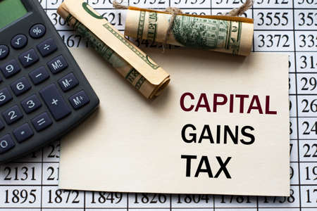 CAPITAL GAINS TAX words on a white sheet against a table with numbers, banknotes and calculator. Business and finance concept