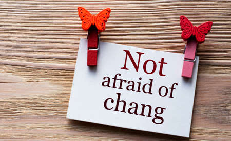 NOT AFRAID OF CHANG - word on a white sheet with beautiful clothespins on a wooden background. Technology concept