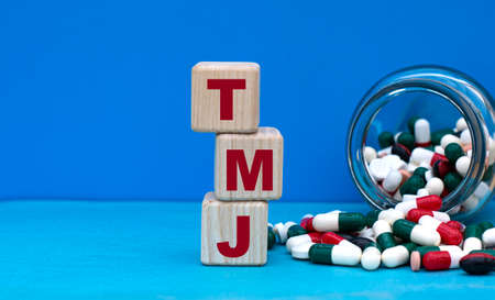 TMJ word on cubes on a blue background with a jar of tablets. Medical concept.