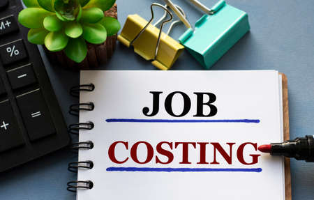JOB COSTING words is written in a notebook with a marker, calculator, clamps and cactus. Business and finance concept