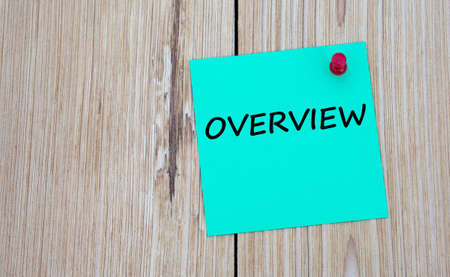 OVERVIEW - word written on a green sheet for notes, which is pinned to a light wooden board. Business concept