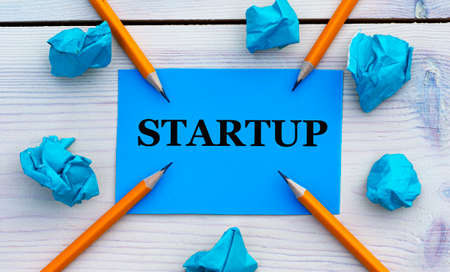 STARTUP - word on blue paper on a light background with crumpled pieces of paper and pencils. Business concept