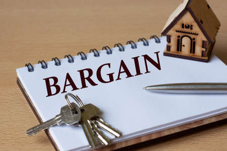 BARGAIN - the word is written in a notebook with a pen, a wooden house and keys. Business and finance concept.