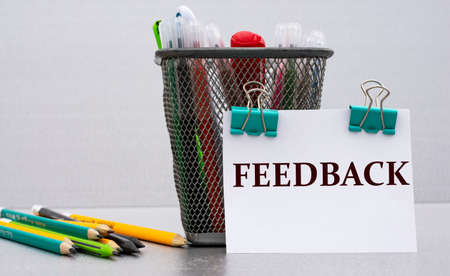FEEDBACK - word on a white sheet with clips against the background of cans of pencils. Business and education concept.