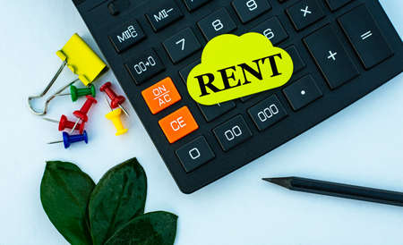 RENT - word on yellow note sheet on white background with calculator, pencil, green sheet and paper clips. Business concept