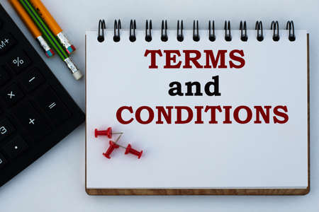 TERMS and CONDITIONS - words on a white sheet of notepad with buttons, pencils, calculator. Business and technology concept