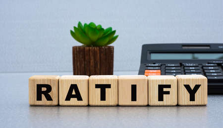RATIFY - word on wooden cubes against the background of calculator and cactus. Business concept