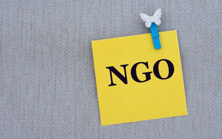 NGO (Non-governmental organization) - word on yellow paper with clothespin on gray background. Business concept