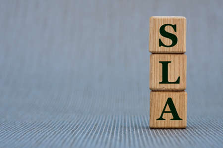 Wooden Blocks The Word SLA (Service Level Agreement). Business concept