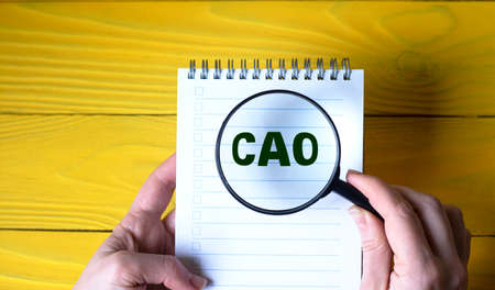 A woman's hand holds a magnifying glass over the word CAO on a yellow wooden background. Business concept Banque d'images