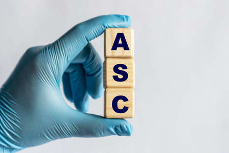 ASC (Ambulatory Surgery Center) is an acronym on cubes held by a hand in a blue glove. Medical concept.