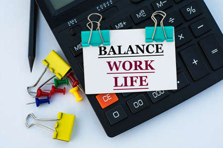 BALANCE WORK LIFE - words on a white sheet with clips on a white background with a calculator, buttons and yellow stationery clips. Business concept