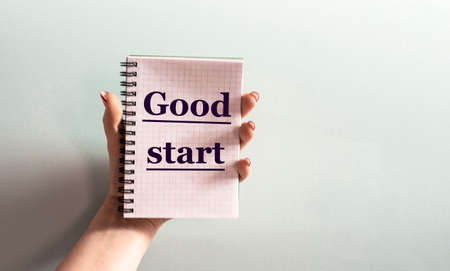 A woman's hand holds a notepad with the word GOOD START on a light background. Business concept