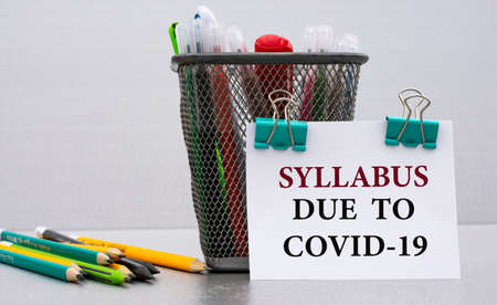 SYLLABUS DUE TO COVID-19 - word on a white sheet with clips against the background of cans of pencils. Business and education concept.