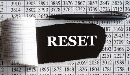 RESET is the word behind torn office paper with numbers and a black pen. Business concept