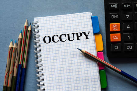 OCCUPY - word in a notebook. Nearby are pills on a gray background. Business concept
