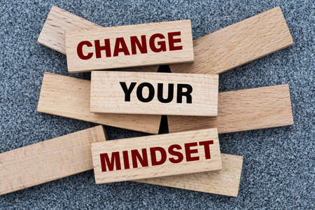 CHANGE YOUR MINDSET - words on wooden bars on a gray background with a free space. Business concept